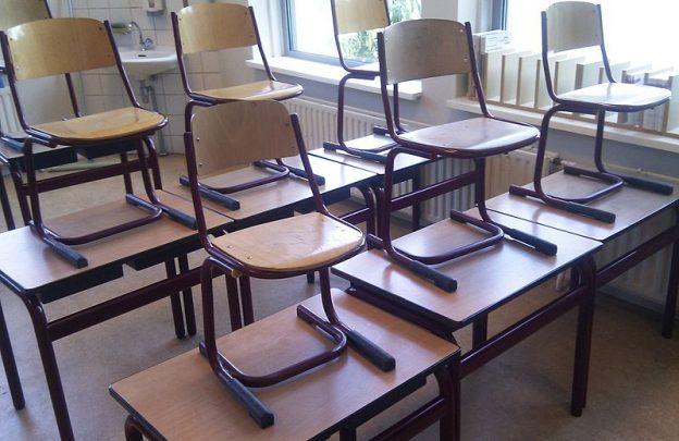 An empty classroom with chairs on the desks