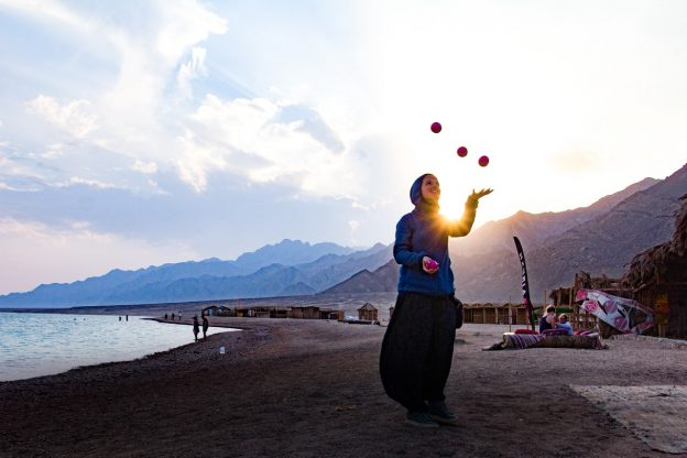 woman juggling with the sun behind her