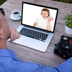 Man watching online briefing on laptop
