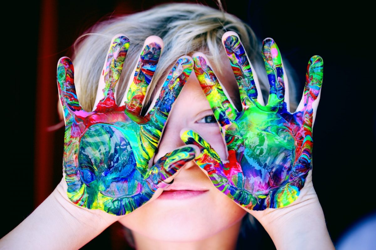 Child with mixed colour paints on their hands